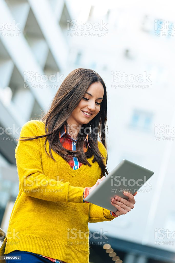 Beautiful hard-working modern businesswoman using digital tablet and smiling stock photo