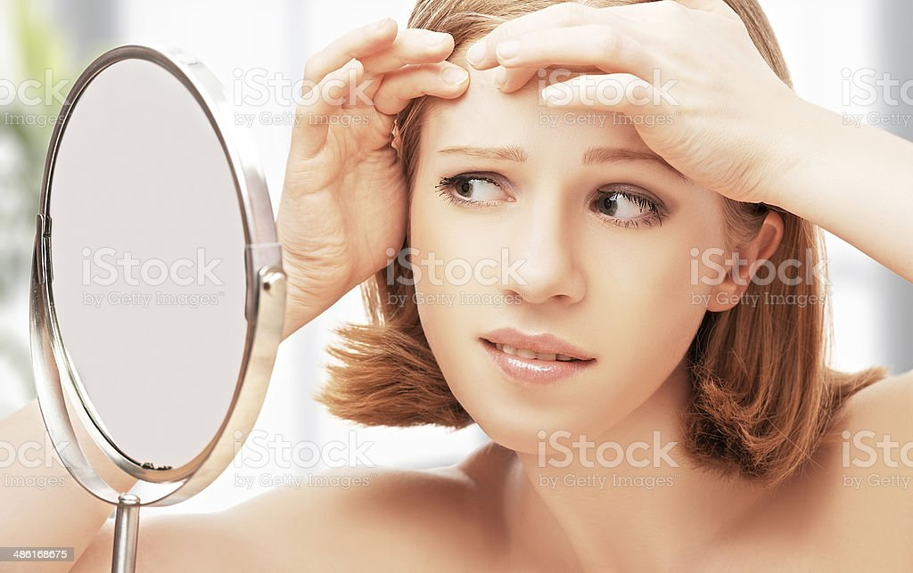 beautiful healthy woman  frightened saw in the mirror acne stock photo