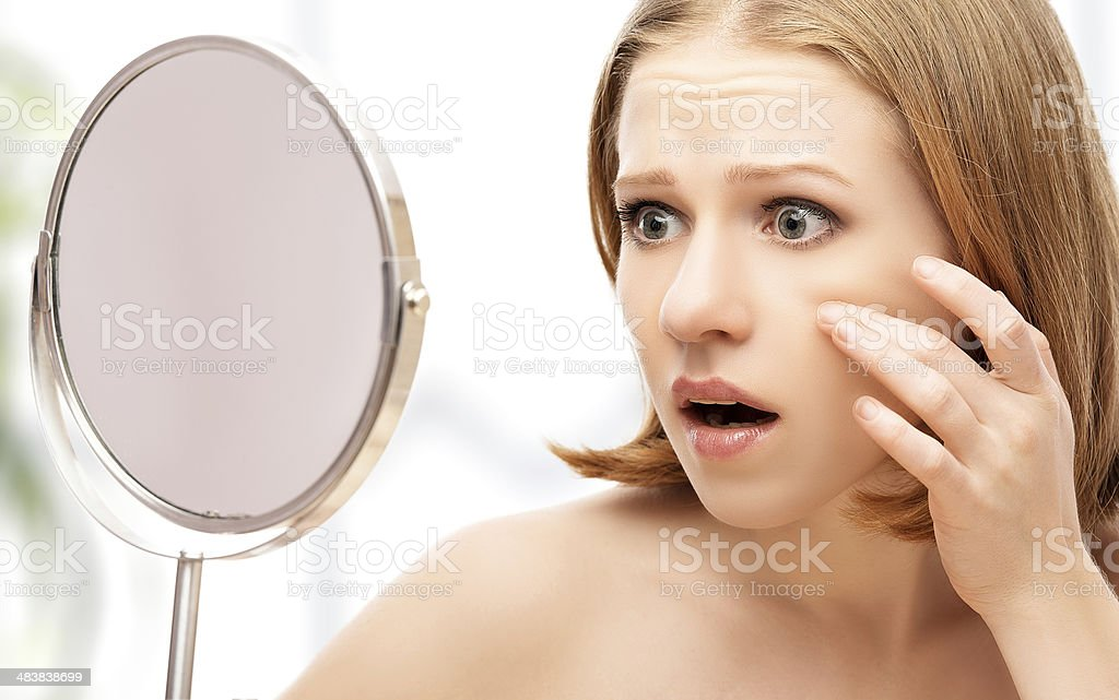 beautiful healthy woman  saw in the mirror acne and wrinkles stock photo