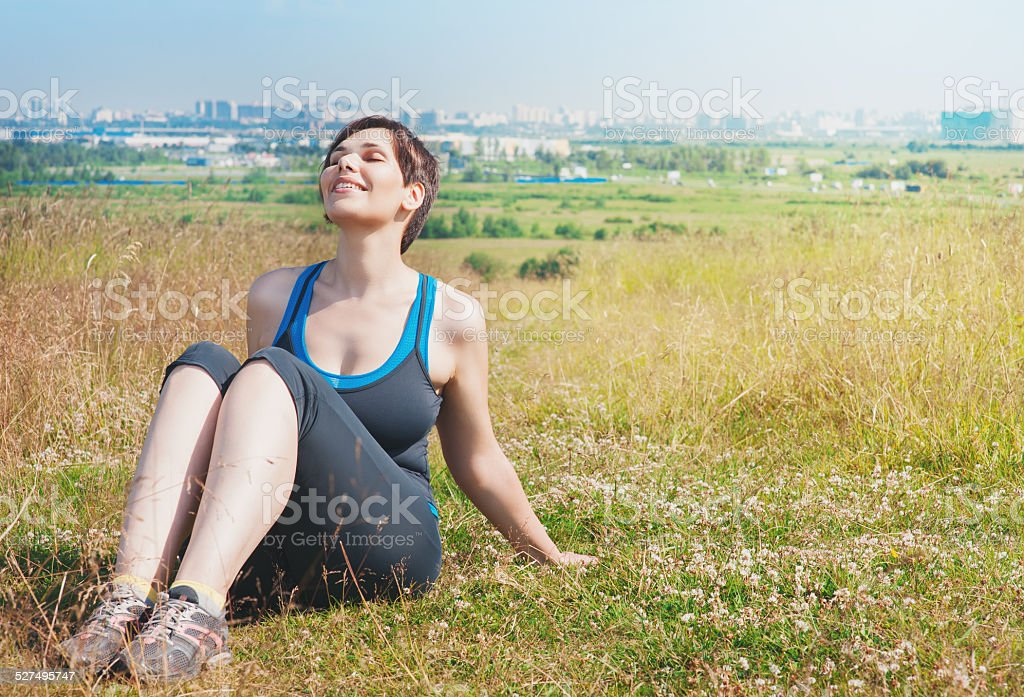Beautiful healthy woman sitting on the meadow outdoor stock photo