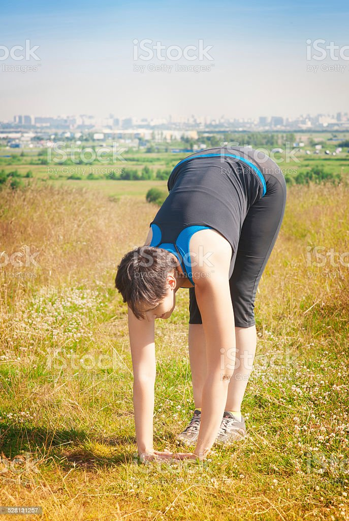 Beautiful healthy woman stretching outdoor stock photo