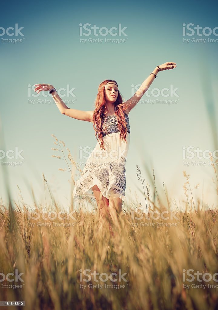Beautiful hippie girl dancing in the field at sunset time stock photo