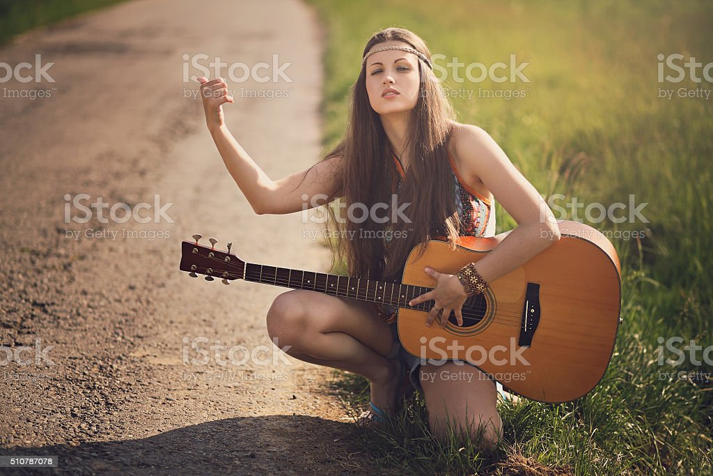Beautiful hippie hitch-hiker with guitar stock photo