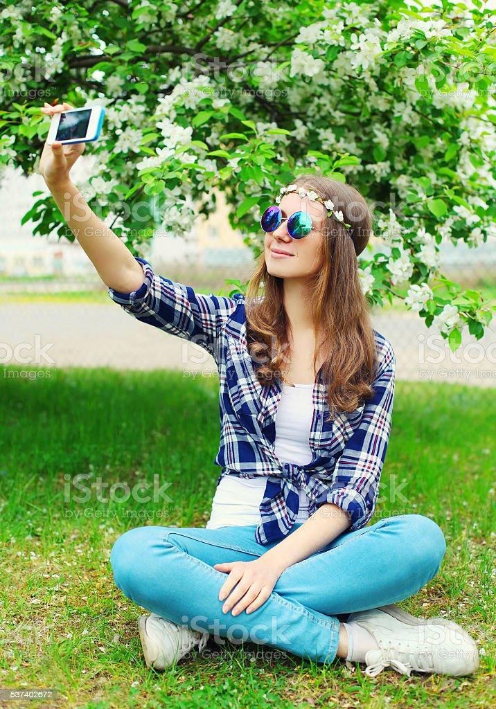 Beautiful hippie woman makes self-portrait on smartphone stock photo