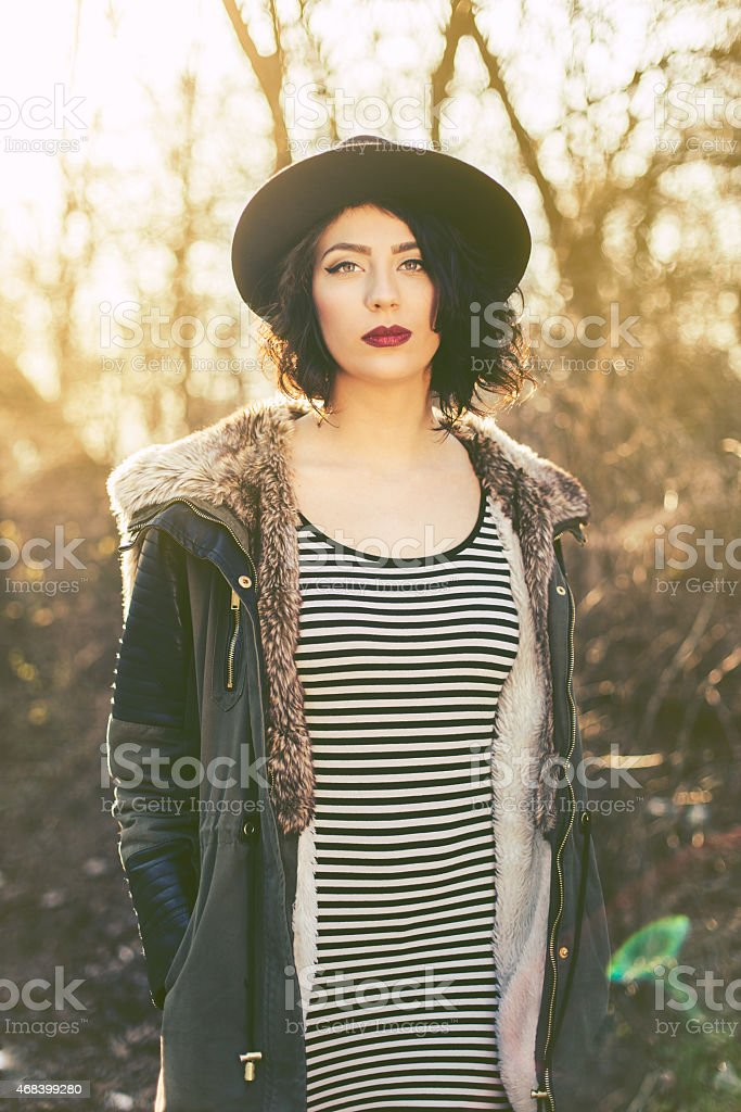 Beautiful hipster girl with hat wearing sunglasses in bright sunlight stock photo