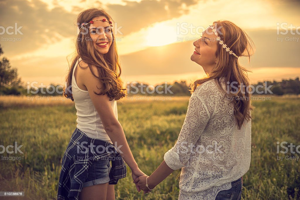 Beautiful hipsters in field at sunset stock photo