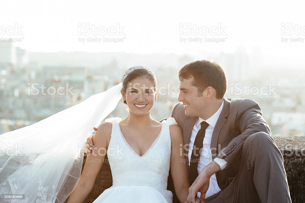 Beautiful Hispanic bride and groom on rooftop stock photo