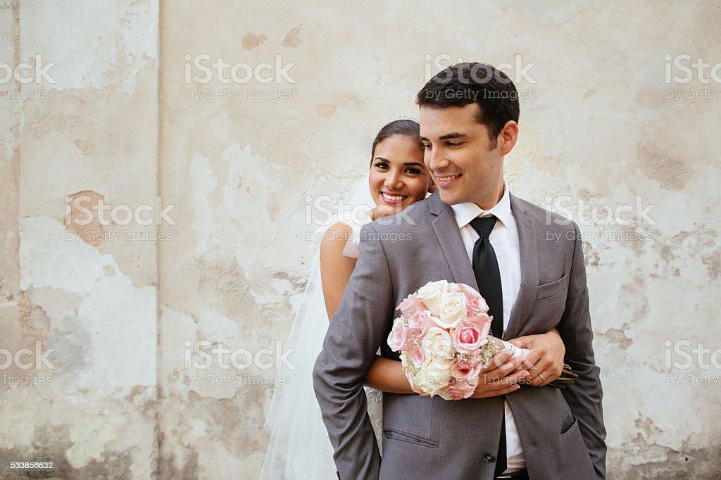 Beautiful Hispanic bride holding her groom stock photo