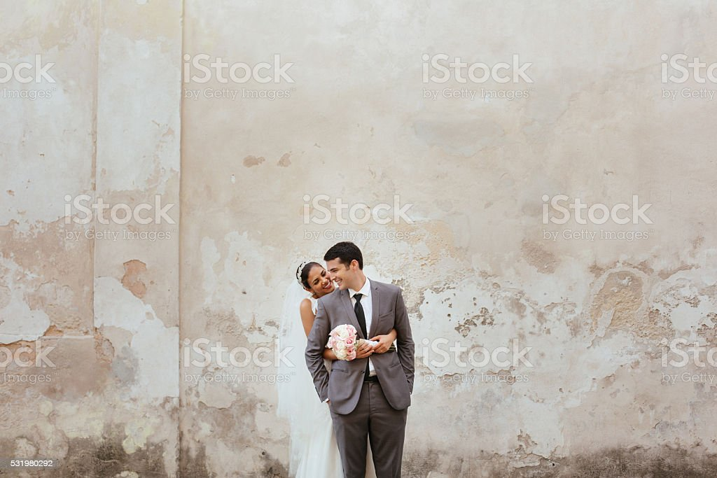 Beautiful Hispanic bride holding her husband tightly stock photo
