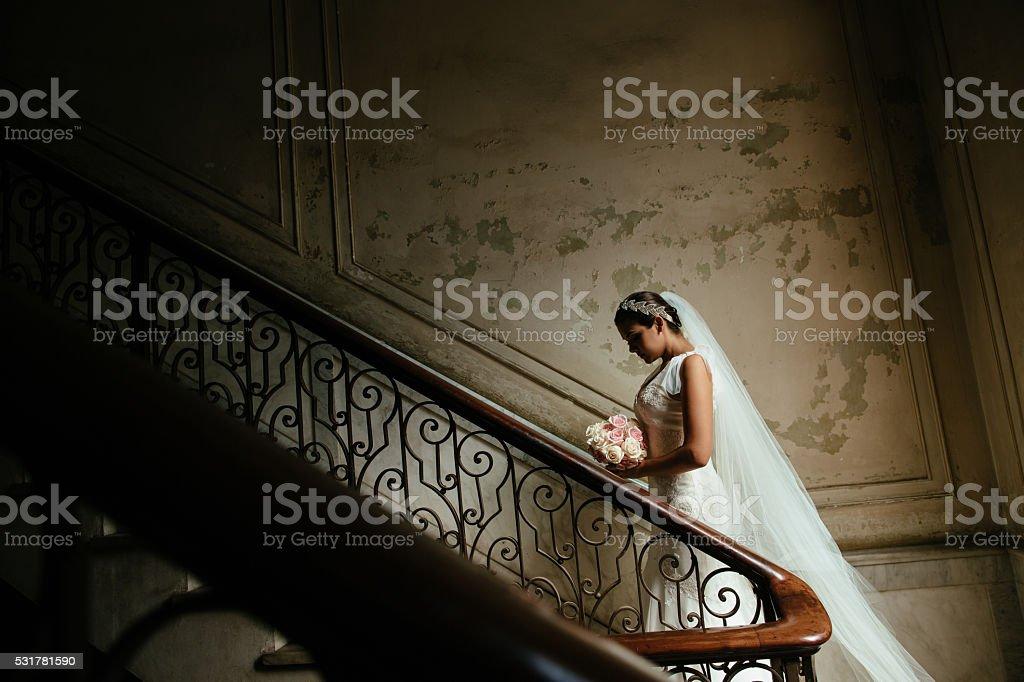 Beautiful Hispanic bride standing on stairway stock photo