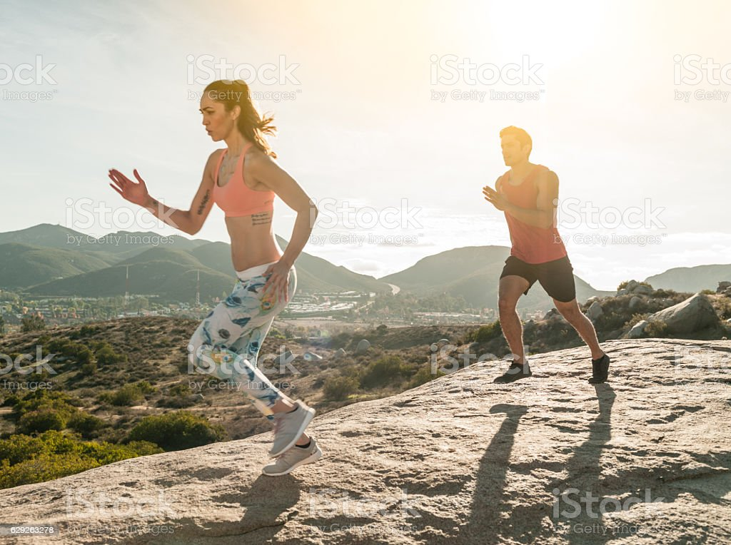 Beautiful Hispanic Couple Running Out Outdoors stock photo