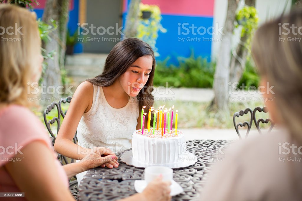 Beautiful Hispanic girl blowing out her birthday candles stock photo