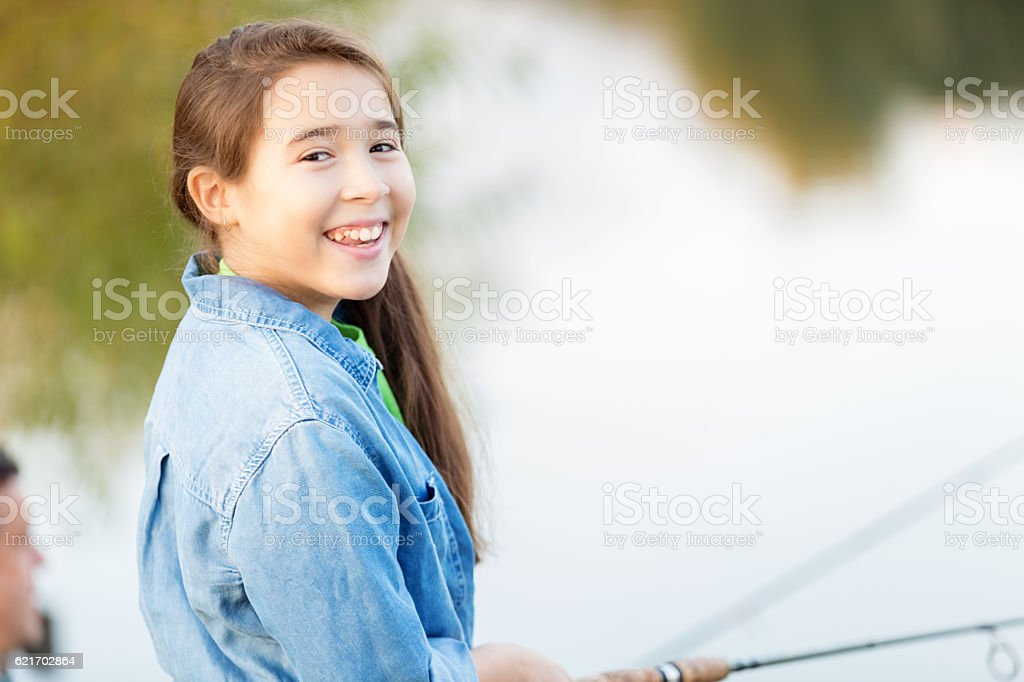 Beautiful Hispanic girl fishes at a pond stock photo