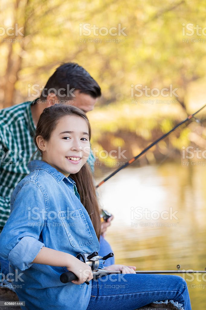 Beautiful Hispanic girl fishes with her grandfather stock photo