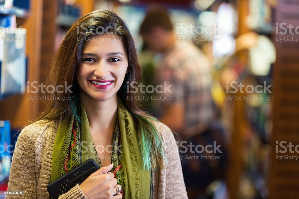 Beautiful Hispanic hipster female college student in library stock photo