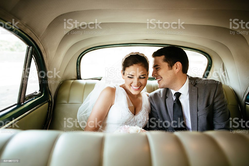 Beautiful Hispanic newlyweds laughing in backseat stock photo