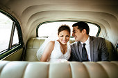 Beautiful Hispanic newlyweds laughing in backseat