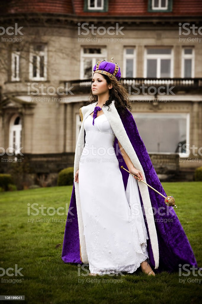 Beautiful Hispanic Young Woman as Queen Outside Castle stock photo