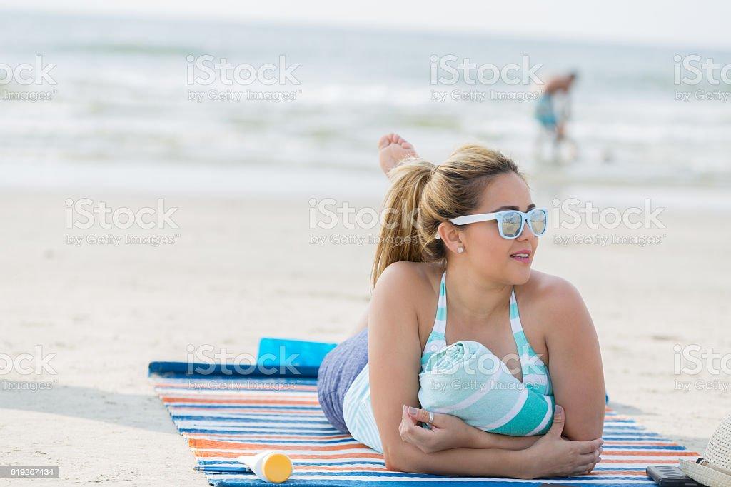 Beautiful Hispanic woman sunbathes on a beach stock photo