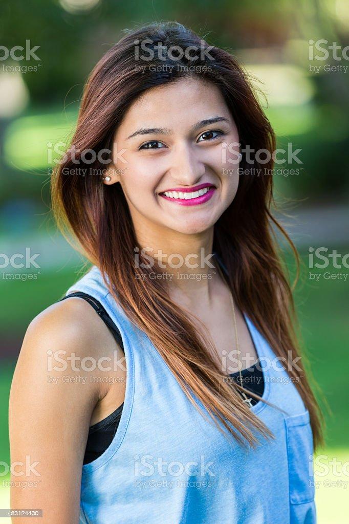 Beautiful Hispanic young woman smiling outdoors stock photo