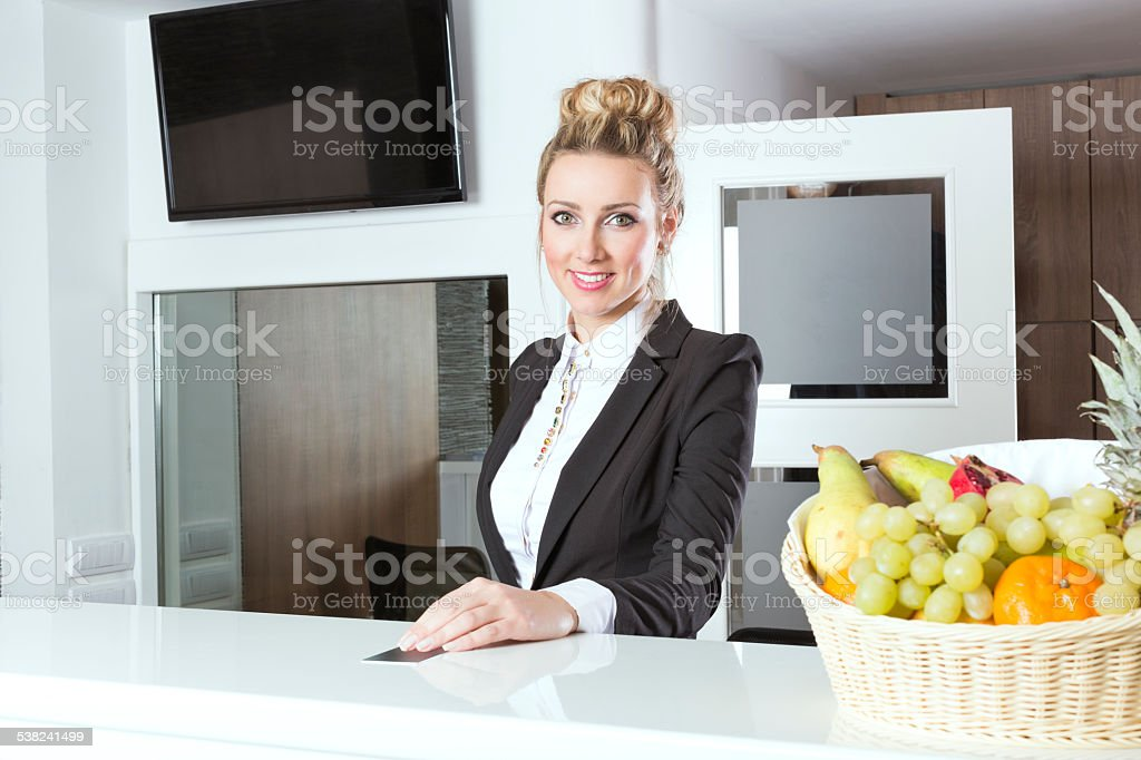 Beautiful hotel receptionist handing out key stock photo