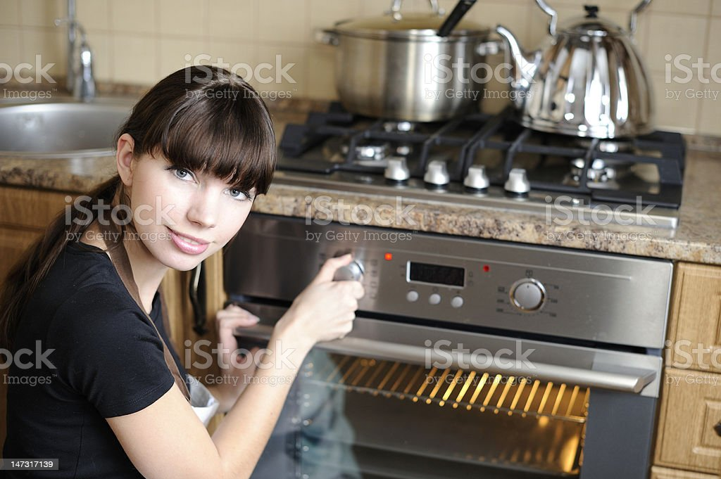 Beautiful housewife switching the oven royalty-free stock photo