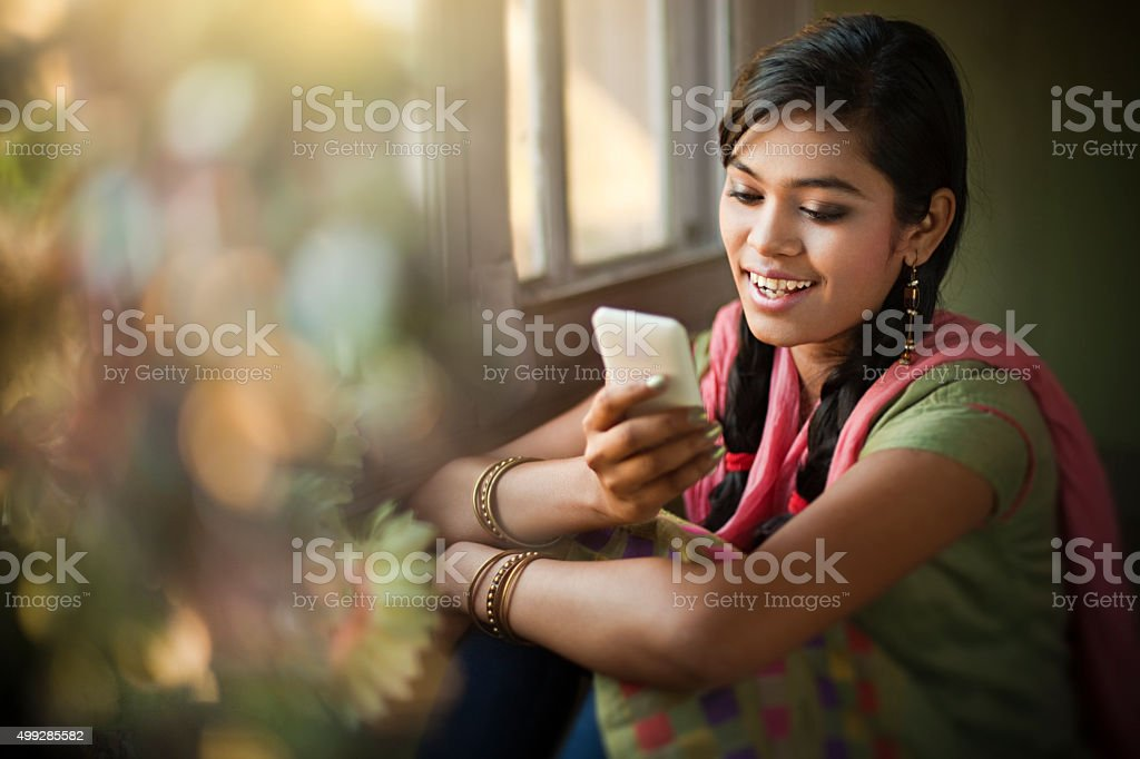 Beautiful Indian girl reading SMS at the time of festival. stock photo