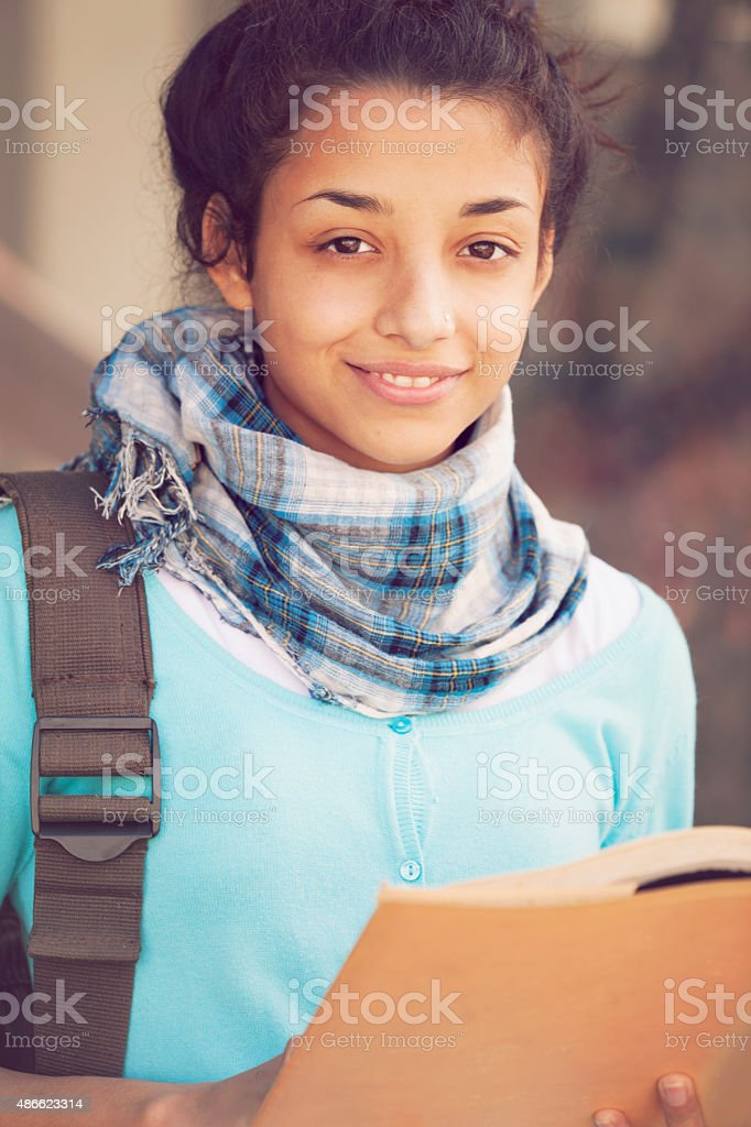 Beautiful indian girl smiling with book stock photo
