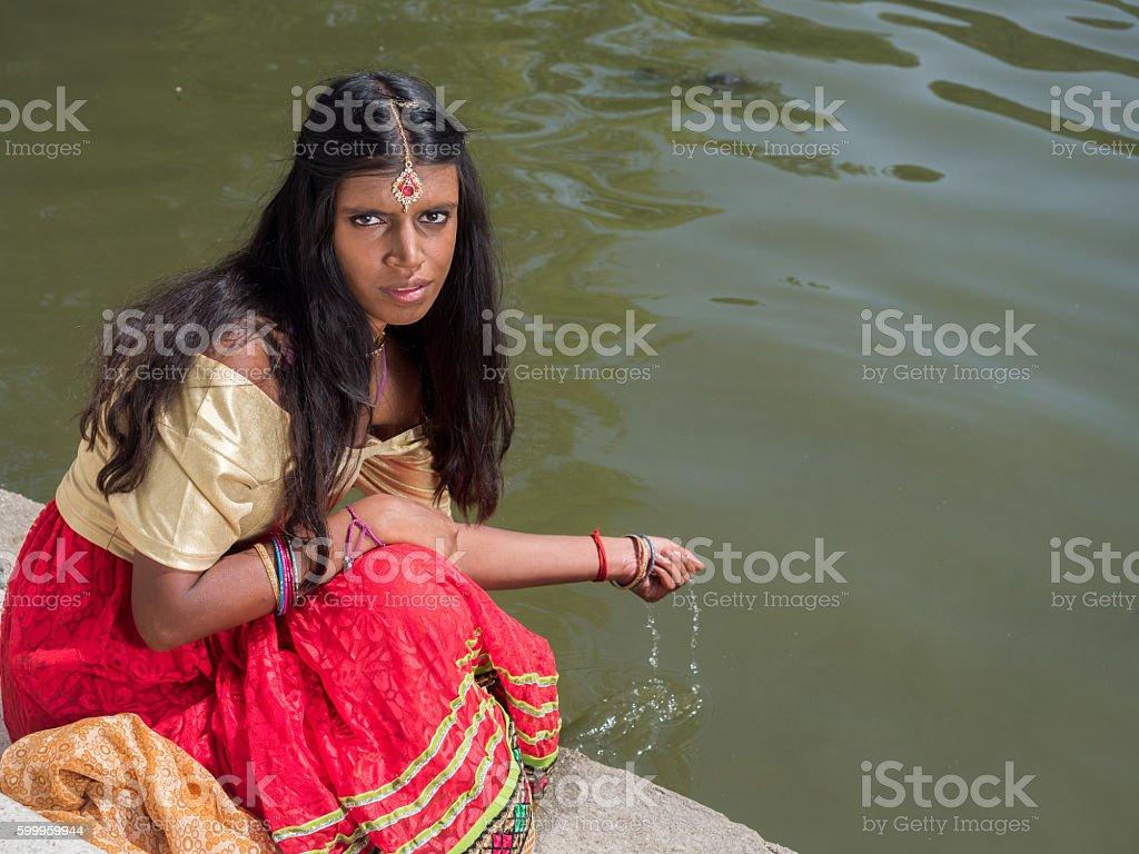 Beautiful indian princess sitting at the lake shore stock photo