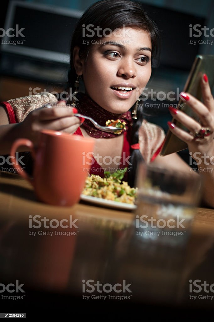 Beautiful Indian woman having snack with coffee and using smartphone. stock photo