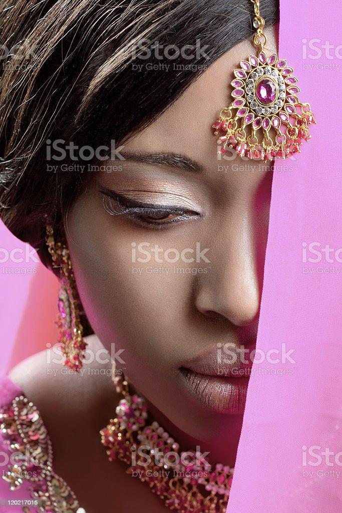Beautiful indian woman wearing golden jewelry royalty-free stock photo