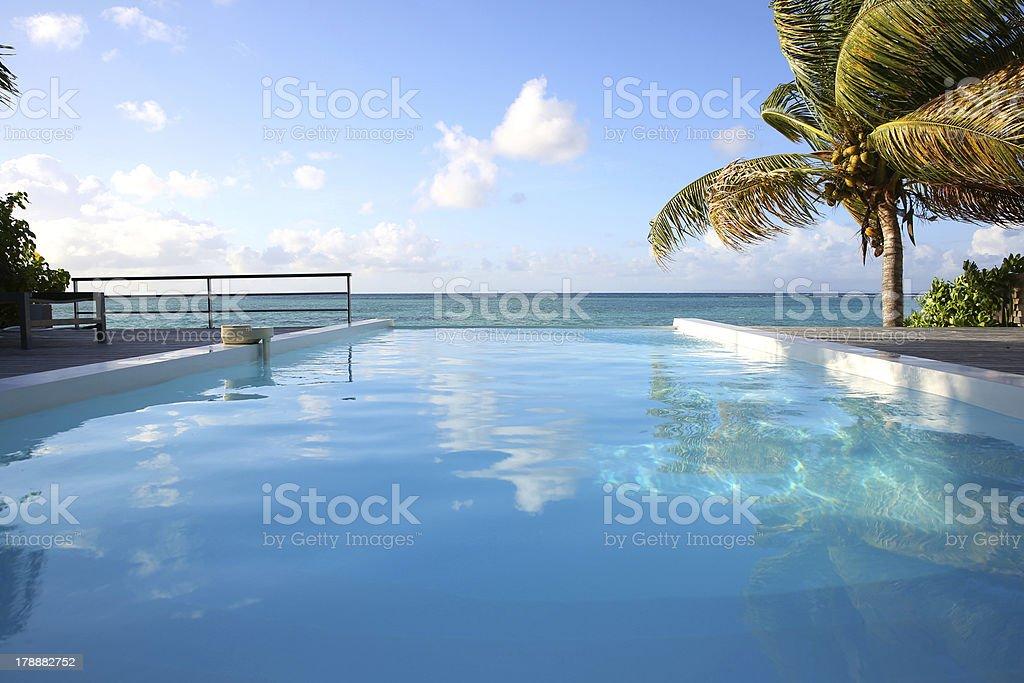 Beautiful infinity swimming pool above blue sea stock photo
