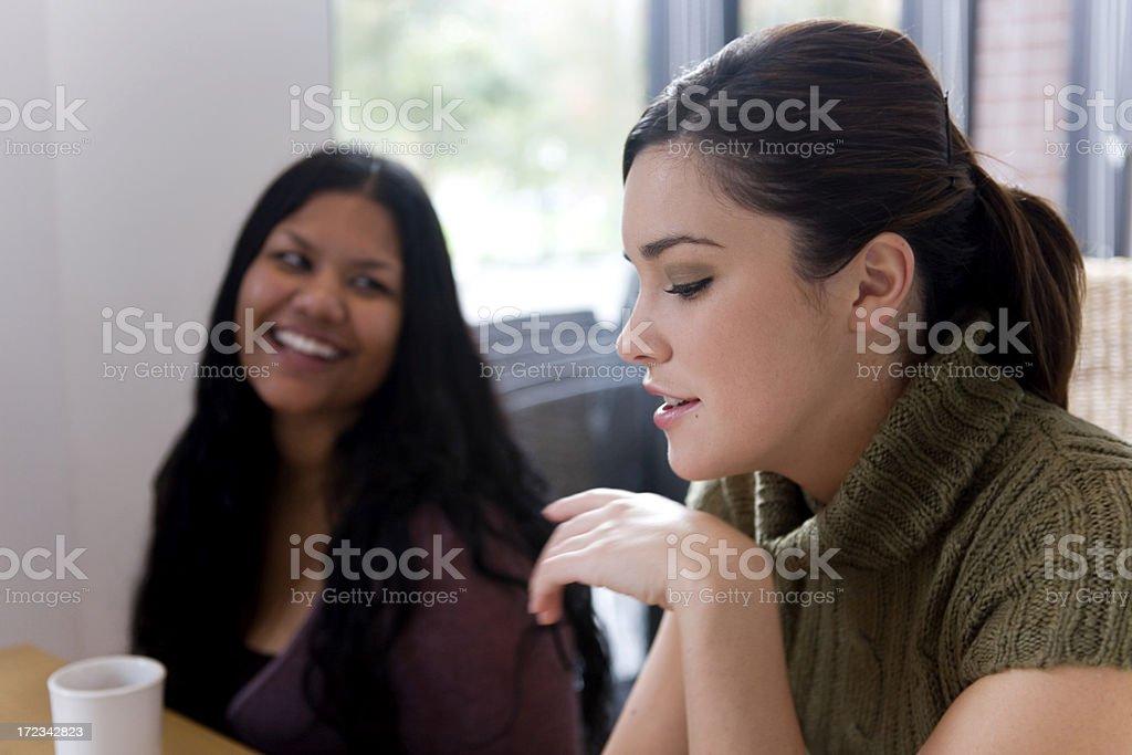Beautiful Interracial Young Women Talking as Friends in Coffee Shop royalty-free stock photo