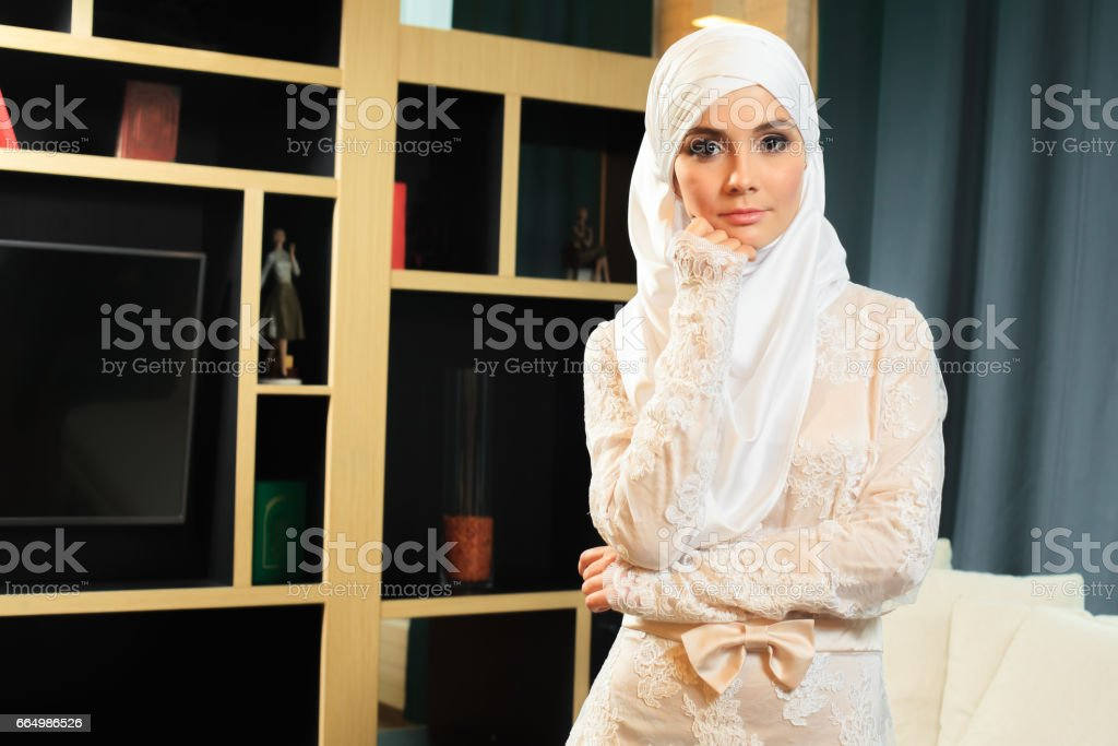 Beautiful Islamic woman in traditional wedding dress, at home stock photo
