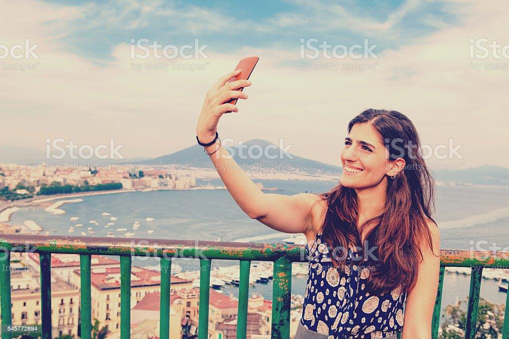 Beautiful Italian Woman taking selfie with Vesuvio and Naples Background stock photo
