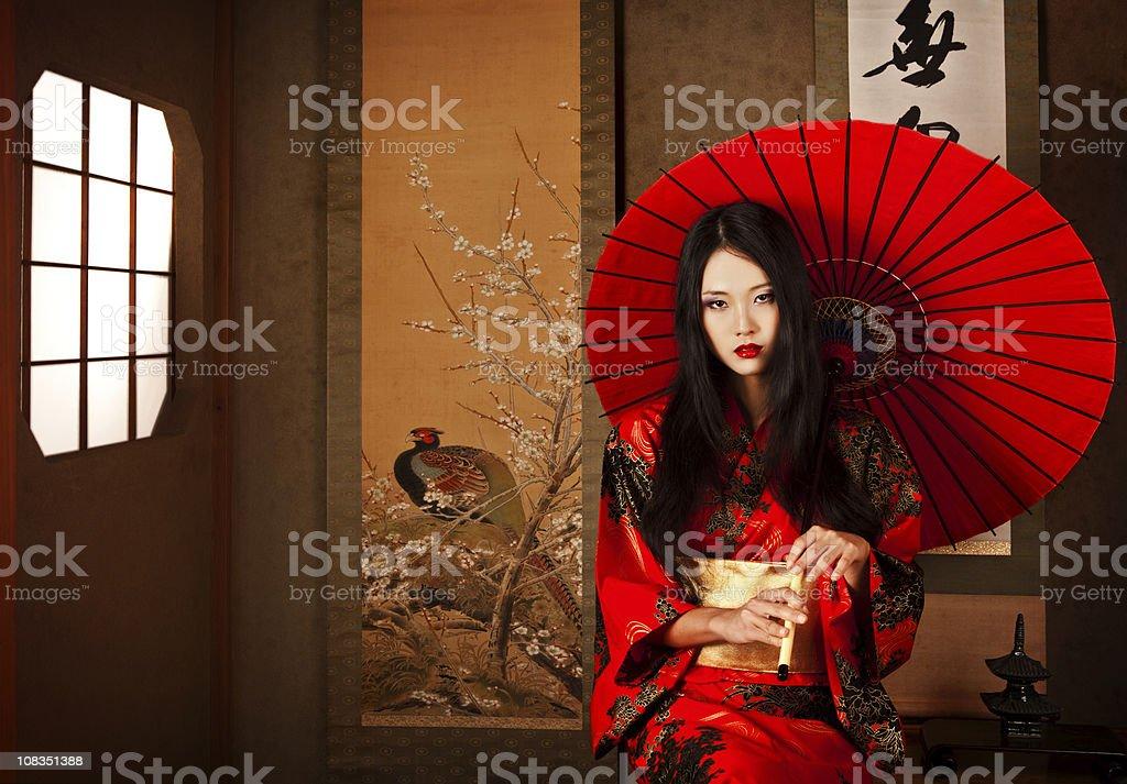 Beautiful Japanese geisha with a red umbrella royalty-free stock photo