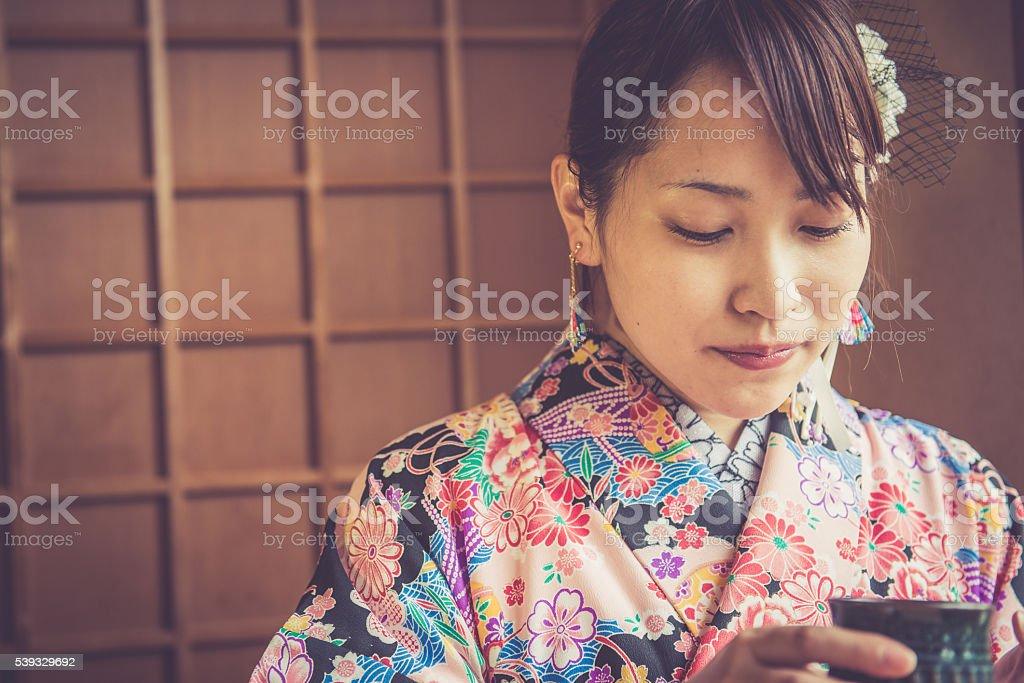 Beautiful Japanese Woman in Kimono Drinking Matcha Tea, Kyoto, Japan stock photo