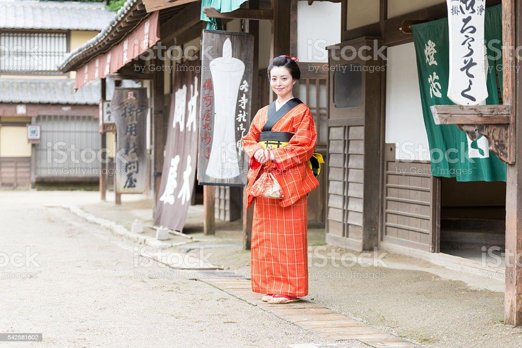 Beautiful Japanese Woman in Kimono smiling in Edo Period Town stock photo