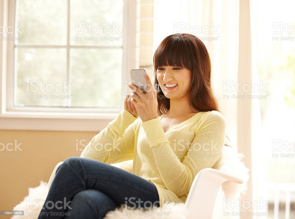 Beautiful Japanese woman using mobile phone sending text message royalty-free stock photo
