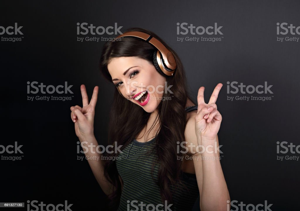 Beautiful joyful young woman listening the music in wreless headphone and showing victory v-sign gesture by two handson on dark grey background stock photo