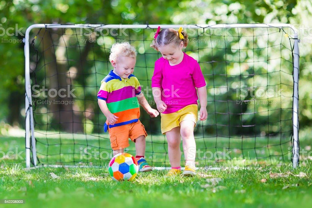 Beautiful kids playing football in school yard stock photo