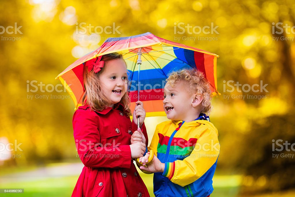 Beautiful kids playing in the rain under colorful umbrella stock photo