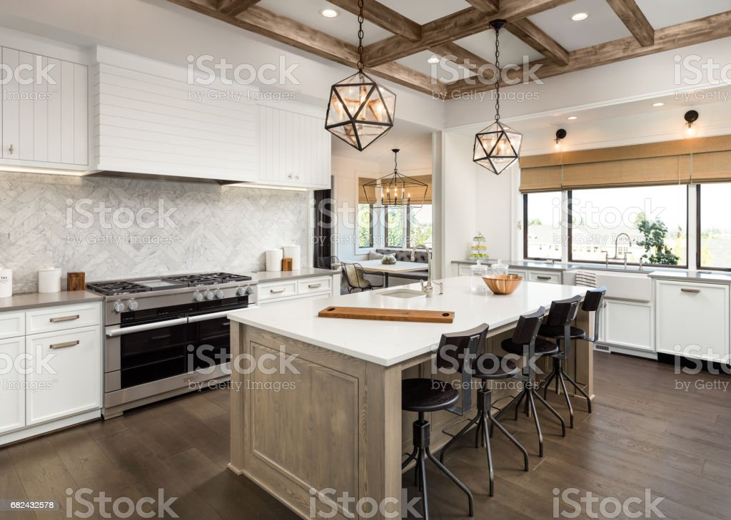 beautiful kitchen in new luxury home with island and pendant light fixtures stock photo