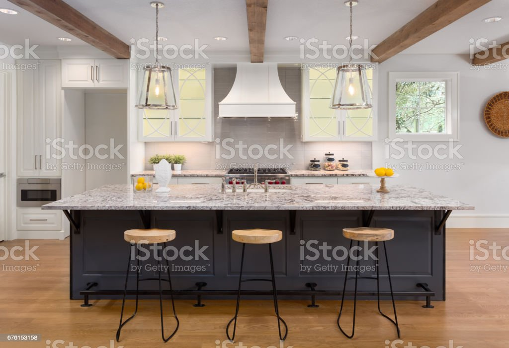 beautiful kitchen in new luxury home with island, pendant lights, and glass fronted cabinets stock photo