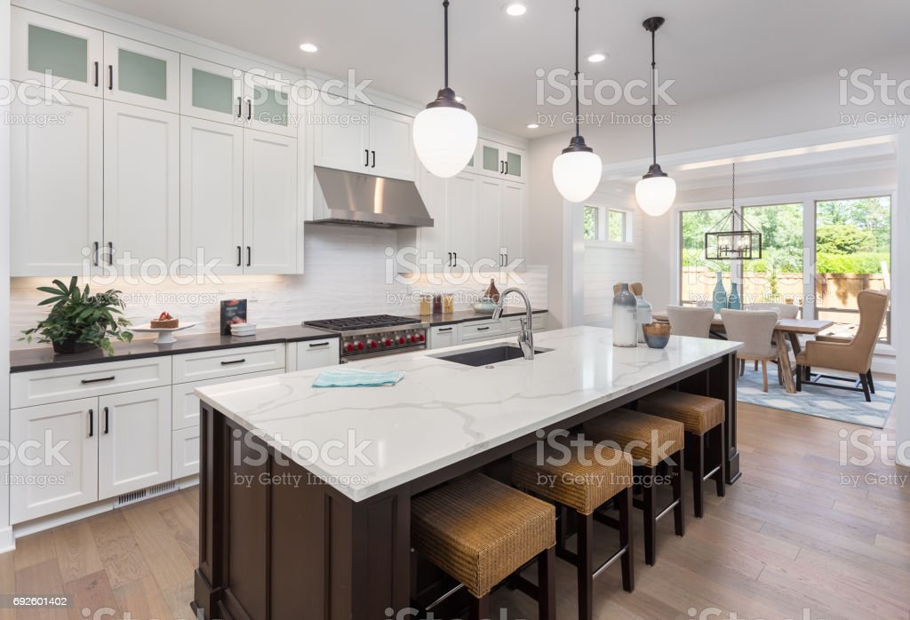 beautiful kitchen in new luxury home with island, pendant lights, and hardwood floors. Includes view of dining room. stock photo