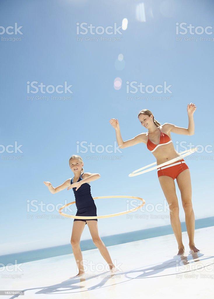 Beautiful lady and girl playing the hula hoop at beach royalty-free stock photo