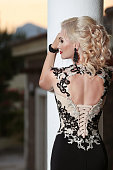 Beautiful lady back in elegant dress. Hairstyle. Red lips makeup