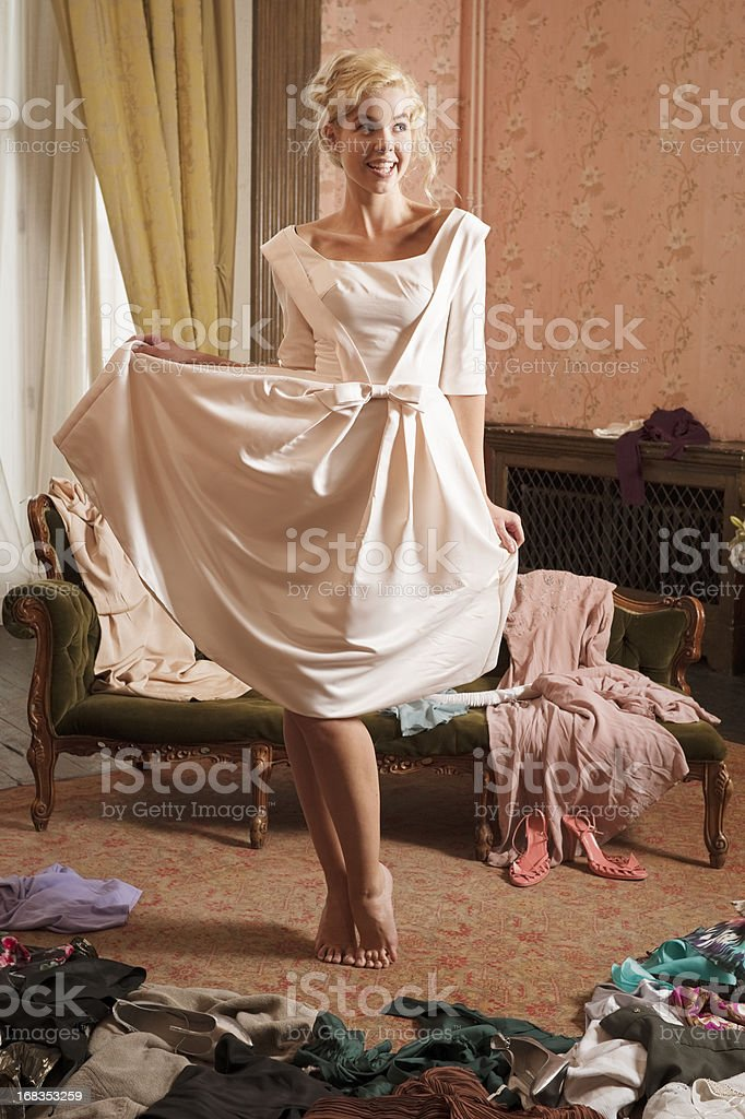 A beautiful lady in a room strewn with dresses stock photo
