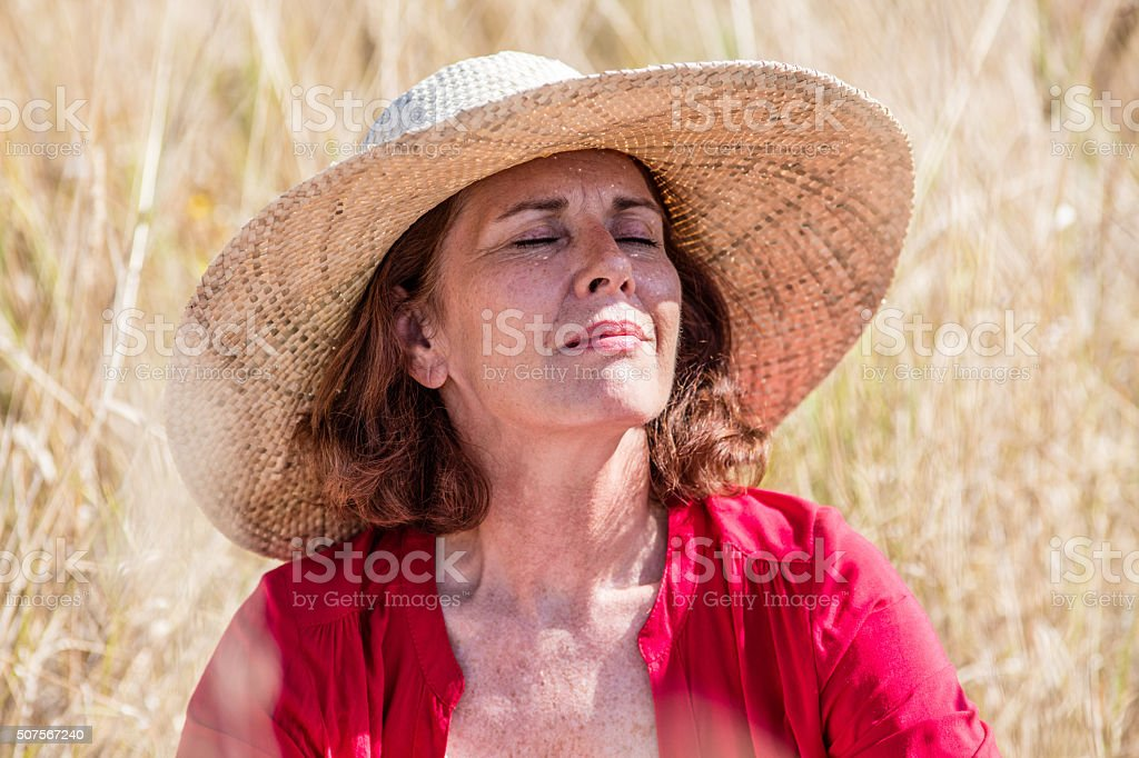 beautiful lady in summer field enjoying warmth with sun protection stock photo