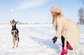 beautiful lady playing with her dog on the snow